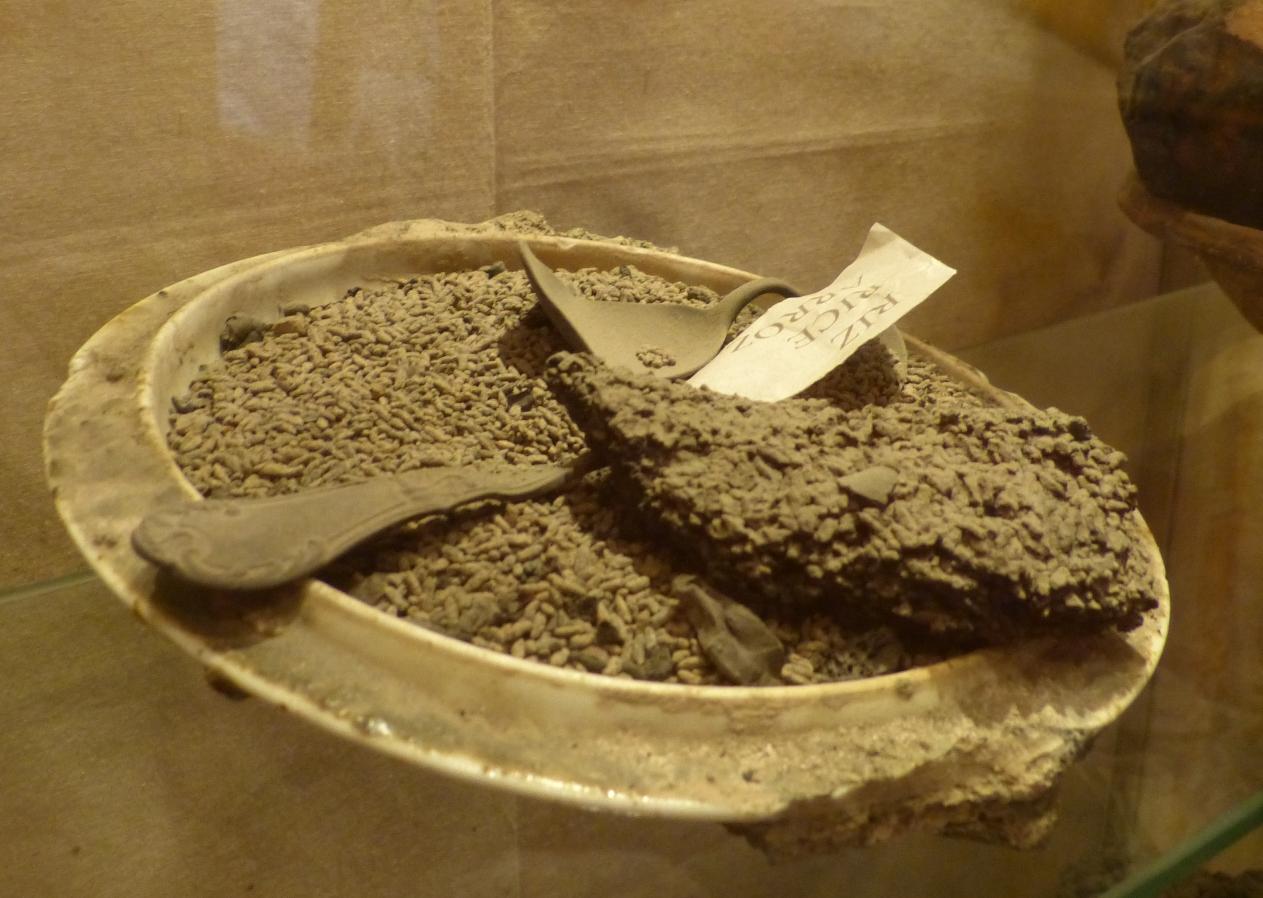 צלחת עם אורז שהתפחם בגלל החום שפגע בעיר. שימו לב שהכף התעוותה לחלוטין